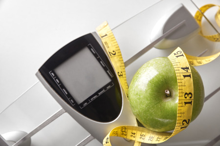 kilos: Scale, apple and tape measure on white table. Weight control concept. Horizontal composition. Top view Stock Photo