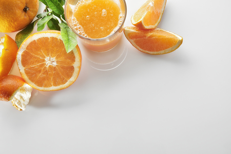 Squeezed orange juice in a glass on a white kitchen table with cut orange. Horizontal composition. Top view.