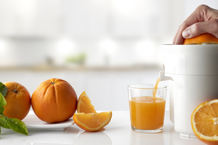 Hand squeezing an orange with an electric juicer in a glass on a white kitchen table. Oranges on a plate and cut. Horizontal composition. Front view.