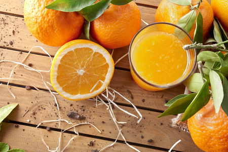 Glass of orange juice on a wooden table with oranges and orange sections. Horizontal composition. Top view