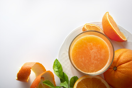 Squeezed orange juice in a glass on plate. On a white kitchen table with cut orange. Horizontal composition. Top view.