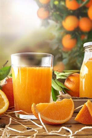 Glas jus d'orange op een houten tafel met een fles en oranje secties. Boom en veld achtergrond met avondzon. Verticale samenstelling. Vooraanzicht Stockfoto