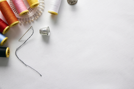 Sewing tools on white fabric background diagonal set.  Horizontal composition. Top view