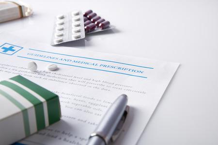 droga: Directrices y prescripci�n m�dica con ampollas de drogas sobre una mesa de cristal blanco. Foto de archivo