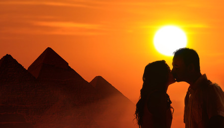 Backlit loving couple honeymoon in Egypt with pyramids and sunset background