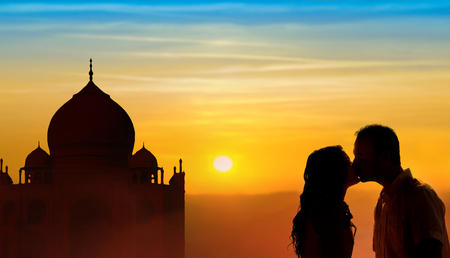 Backlit loving couple honeymoon in India with Taj Mahal and sunset background Stock Photo