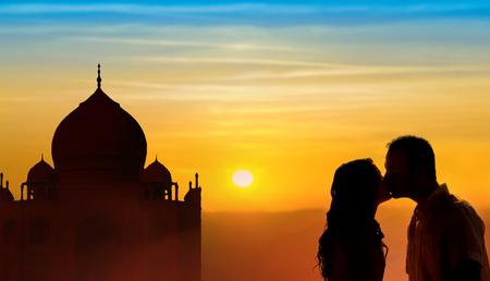 Backlit loving couple honeymoon in India with Taj Mahal and sunset background Imagens