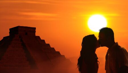 mayan culture: Backlit loving couple honeymoon in Mayan culture with kukulkan temple and sunset background