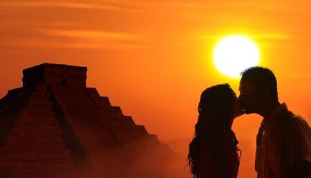 cultura maya: Retroiluminada amantes de la pareja de luna de miel en la cultura maya con el templo de Kukulc�n y el fondo del atardecer
