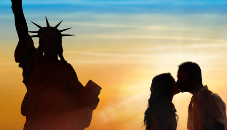 Backlit loving couple honeymoon in New York with liberty statue and sunset background