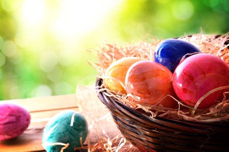 Easter eggs on a wooden table and a basket in the field. Horizontal composition. Elevated view