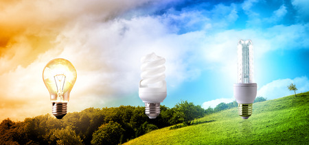 co2 emissions: Comparison between various types of light bulb on landscape background. CO2 emissions and environmental conservation. Horizontal composition. Front view Stock Photo