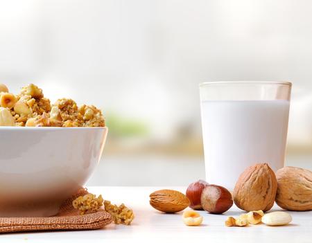 台所でドライ フルーツとミルクのガラスが付いている穀物の完全をボウルします。フロント ビュー