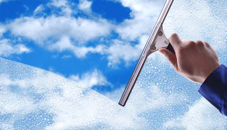 Employee hand cleaning a glass with rain drops and blue sky background.Concept and background window cleaning. horizontal composition