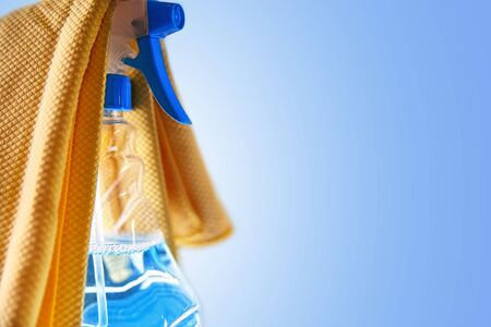 Glass cleaner spray bottle and yellow cloth with blue background. Cleaning concept.Horizontal composition.