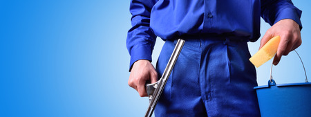 Window cleaning employee with work tools and blue background. Background and concept. horizontal composition.