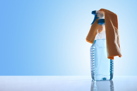 sanitizing: Bottle with glass cleaner and a yellow rag on a white table glass with blue background overview. Front view. Horizontal composition. Stock Photo
