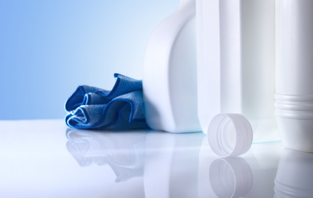 Cleaning products on white table and blue background close up. Front view. Horizontal composition. Archivio Fotografico