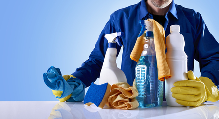 neatness: Cleaning service with products and equipment on a white table and uniformed worker. Front view. Horizontal composition. Stock Photo