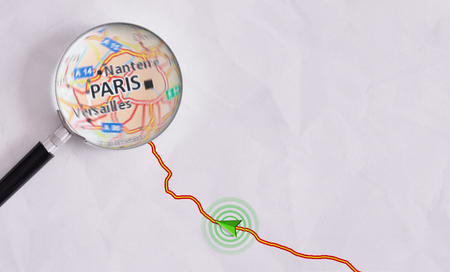 Route on sheet of paper with GPS symbology and magnifying glass highlighting Paris. Concept travel route Stock Photo
