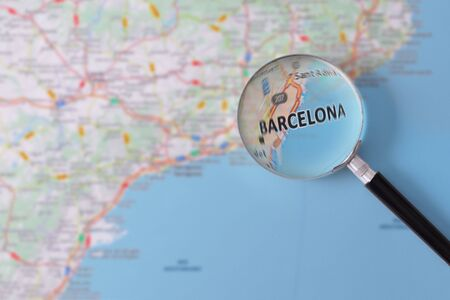 consulted: Map of Barcelona consulted with a magnifying glass highlighting the name of the city Stock Photo