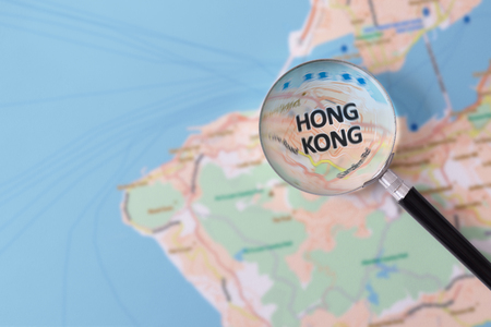 Map of Hong Kong consulted with a magnifying glass highlighting the name of the city