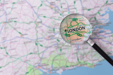 Map of London consulted with a magnifying glass highlighting the name of the city
