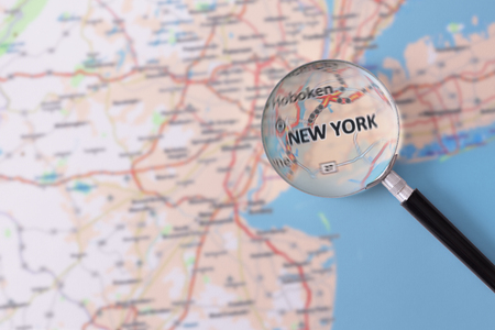 consulted: Map of New York consulted with a magnifying glass highlighting the name of the city Stock Photo