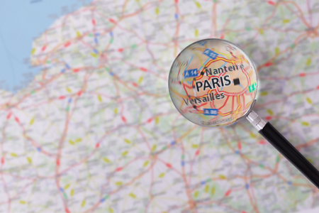 consulted: Map of Paris consulted with a magnifying glass highlighting the name of the city