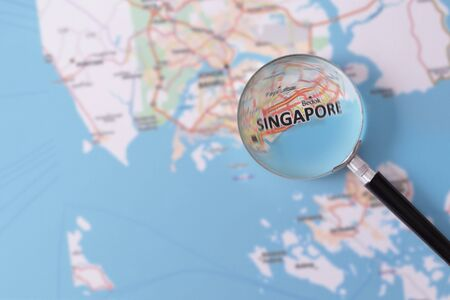 consulted: Map of Singapore consulted with a magnifying glass highlighting the name of the city Stock Photo