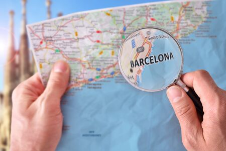 Hands picking up a map of Barcelona and looking for a location with a magnifying glass with representative monument in the background. Stock Photo