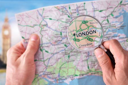 triptico: Manos que toman un mapa de Londres y en busca de un lugar con una lupa con el monumento representativo en el fondo. Foto de archivo