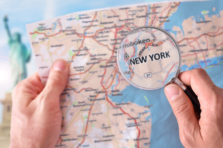 Hands picking up a map of New York and looking for a location with a magnifying glass with representative monument in the background. Stock Photo