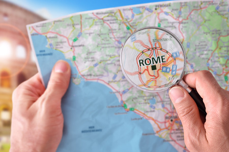 Hands picking up a map of Rome and looking for a location with a magnifying glass with representative monument in the background.