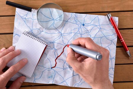 hands tracing a path on map on a wooden table. With pen notepad and magnifying glass. Top view Stock Photo