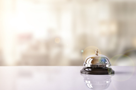 Hotel service bell on a table white glass hotel and simulation background. Concept hotel, travel, room