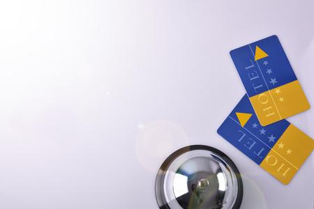 campanas: servicio de alarma del hotel y el acceso cuarto de la tarjeta en un vidrio blanco de mesa. concepto de hotel, viajes, habitación. Vista superior Foto de archivo