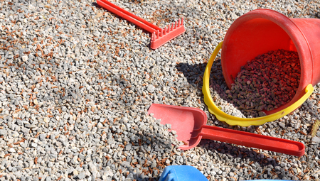 playpen: Rake, shovel and bucket child on playground gravel.Horizontal composition.