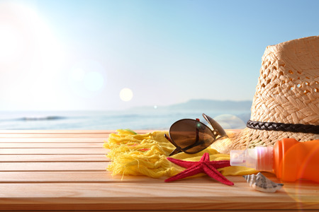 articles: Beach articles on a table wooden slats and sea background with sunbeam. Horizontal composition. Front view. Stock Photo