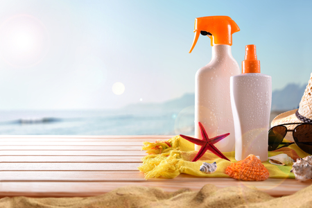 Suncream on towel and wooden slats with shells. Sun shine and sea background. Horizontal composition. Front view Imagens