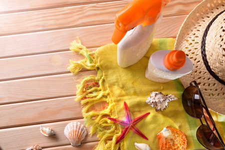 suncream: Two spray suncream on towel and wooden slats with shells. Horizontal composition. Top view