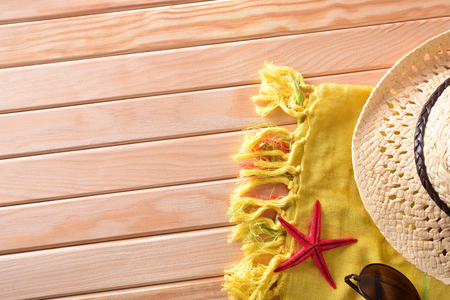 articles: Articles of Beach on wooden slats.Sunglasses, hat and towel.  Horizontal composition. Top view
