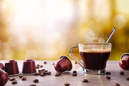 decaffeinated: Cup of coffee with capsules and bainas and local background. Front view