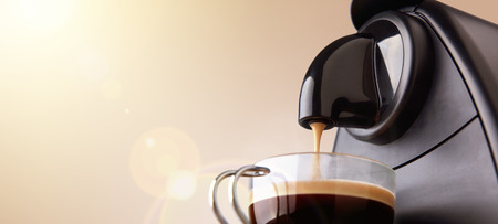Espresso machine making coffee in a glass cup and beige gradient background. Low level, panoramic view Foto de archivo