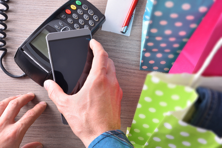 contactless: Payment in a trade with mobile phone. Top view,vertical composition