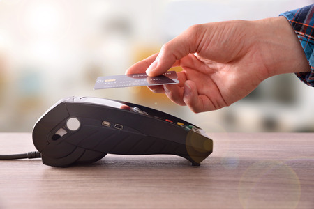 Payment on a trade through contactless card and NFC technology. Front view. Horizontal composition. Archivio Fotografico