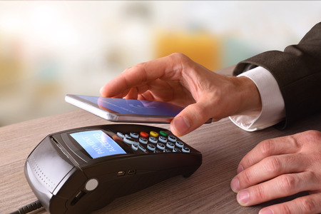 Payment on a trade through mobile and NFC technology. Elevated view. Horizontal composition.