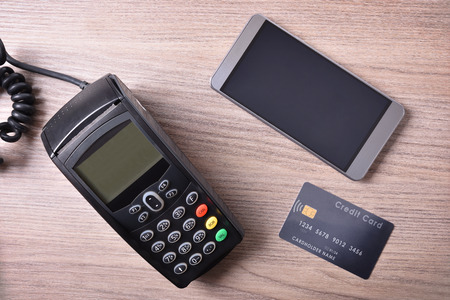 contactless: Mobile phone and credit card on wood table. Concept of payment system. Top view Stock Photo