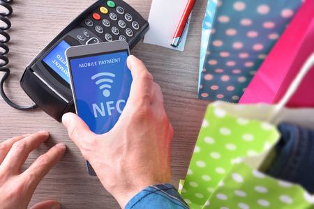 Payment in a trade with nfc system with mobile phone. Top view,vertical composition