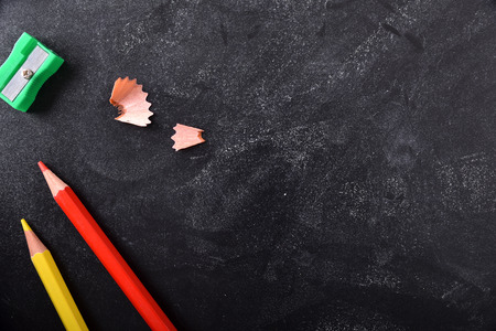 School supplies on the left side on a blackboard with chalk traces and space for title. Top view